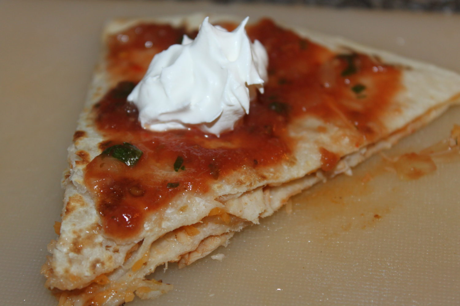 Barbecue turkey quesedilla topped with salsa and sour cream